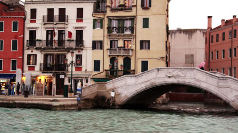 Venetian shops, apartments, and bridge from canal Footage