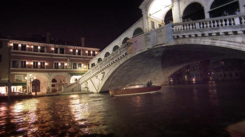 A single motor boat travels underneath the Rialto Bridge Footage