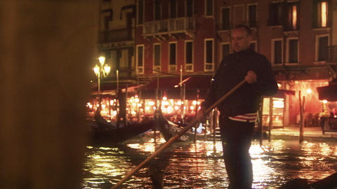 A gondolier paddles his boat on the Grand Canal at night Footage