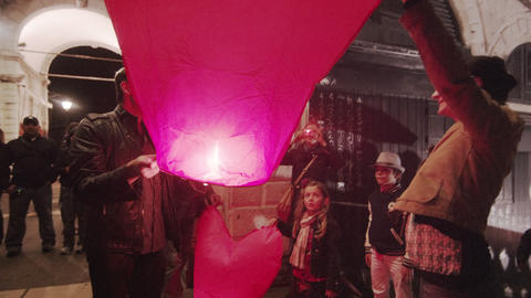 Two people hold a lit, hear-shaped paper lanter Footage