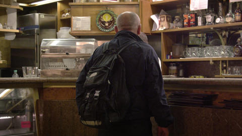 Static then panning shot of a man ordering at an Italian cafe Footage