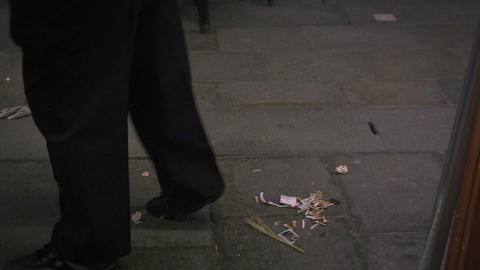 Following shot of a man sweeping up the outdoor eating area at an Italian cafe Footage