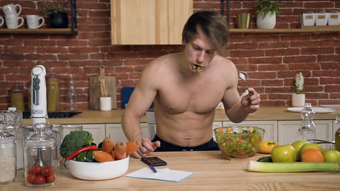 Young guy with naked torso is sitting behind kitchen table eating vegan salad Footage
