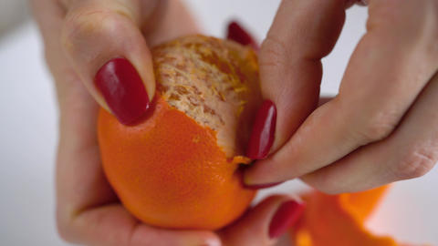 Women's hands peel the peel of tangerine, mandarin slices are piled on a plate Live Action
