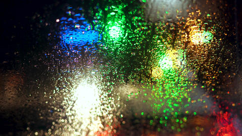 Close up rain drops on car window glass with blurred night city car lights bokeh Live Action