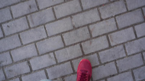 Top view of male legs in sneakers, which go along the sidewalk, meet female legs Live Action