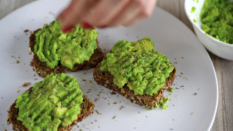 Spreading mashed avocado on toast and sprinkle with salt and spices. Healthy Footage