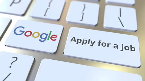 GOOGLE company logo and Apply for a job text on the keys of the computer Footage