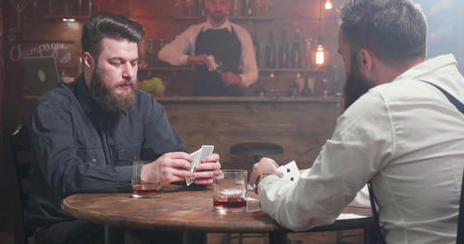 Bearded man having a sip of whiskey while playing cards with a friend GIF