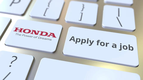HONDA company logo and Apply for a job text on the keys of the computer keyboard Live Action