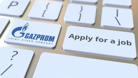 GAZPROM company logo and Apply for a job text on the keys of the computer Live Action