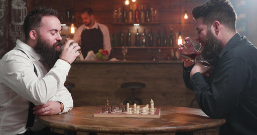 Two stylish men having a conversation over a glass of whiskey and a chess game Footage