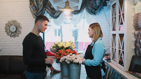 Handsome man come to a flower shop and ask florist about... Stock Video Footage