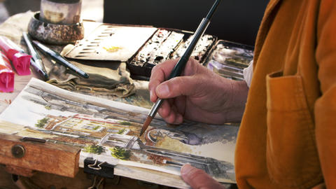 Tilting down shot of artist painting using watercolors a scene of a gondola on a Footage