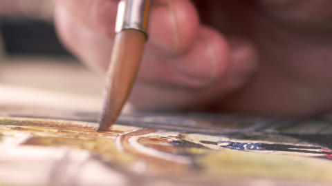Close up shot of artist painting in details of a watercolor painting Footage