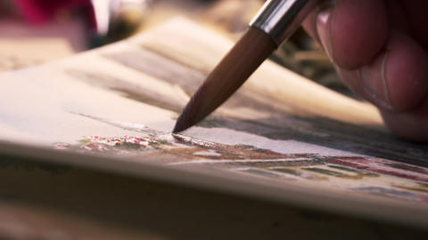 Shot of an artist painting in details in a watercolor painting Footage