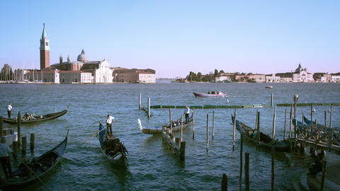 Shot of several gondolas in the canal with the island of San Giorgio Footage