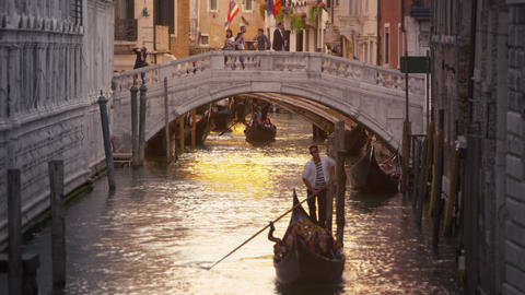 Shot of a gondola in a canal with a bridge behind Footage
