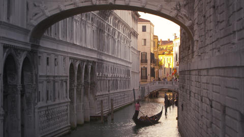 Panning down from the bridge of Sighs to a gondola floating the canal below Footage
