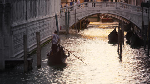 Slow motion shot of gondolier navigating his gondola toward a busy canal bridge  Footage