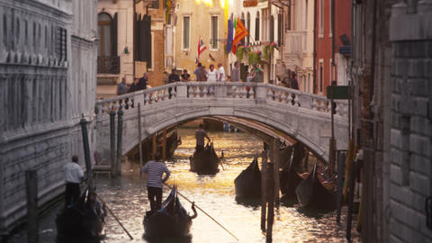 Slow motion shot of gondolas traveling down a canal Footage