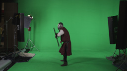 Side shot of man in armor with shield swinging flail through air. Shot against g Footage