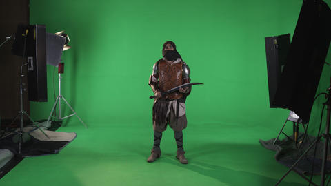 Shot of masked man standing making intimidating motion with black sword. Against Footage