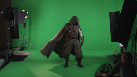Shot of mysterious hooded medieval archer wearing a cloak with bow in hand. Agai Footage