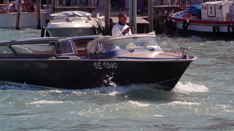 Slow motion shot of man driving black boat in venetian canal Footage