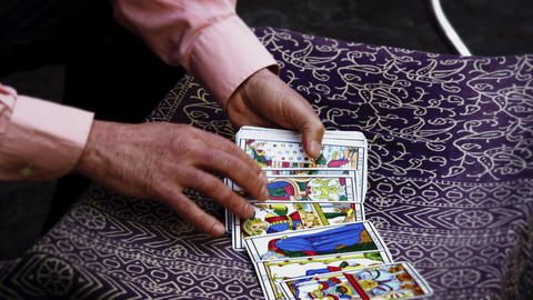 Slow motion shot of tarot card reading fanning cards on table Footage