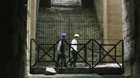 Slow motion footage of people coming in and out of the Colosseum from the inside Footage