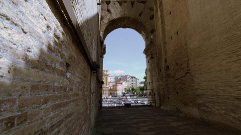Italian buildings and cars seen through a Colosseum arch on a sunny day Footage