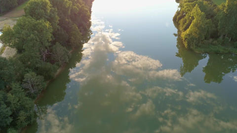 Tilting upwards drone shot reflection sunset sunrise smooth lake sky reflection Footage