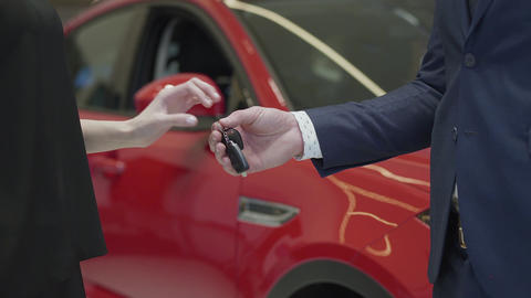 Unrecognized salesman in a business suit gives a car keys to unrecognized Live Action
