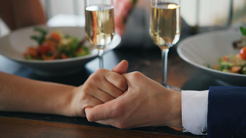 Close-up shot of male hand holding female hand on table with champagne glasses Live Action