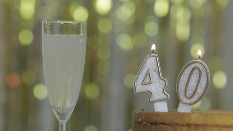 Number 40 birthday celebration candle against a bright lights and golden bokeh background Live Action