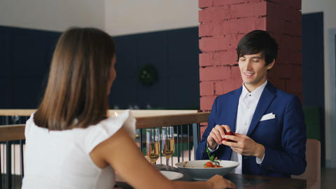 Handsome young man in fancy suit is making proposal to his beloved young woman Live Action