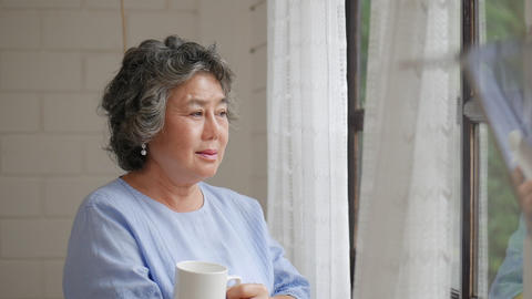 Portrait senior Asian woman drinking tea morning beside a window at home Live Action
