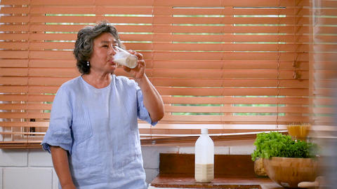 Portrait senior Asian woman drinking milk in the kitchen at home Live Action