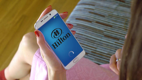 Young woman holding a cell phone with loading Hilton mobile app. Conceptual Footage