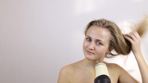 Blonde cares for hair and blow-dry them Footage