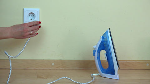 woman hand plug iron wire to wall socket Footage