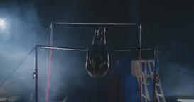 In slow motion in the smoke girl acrobat on the crossbar performs rotation and Footage
