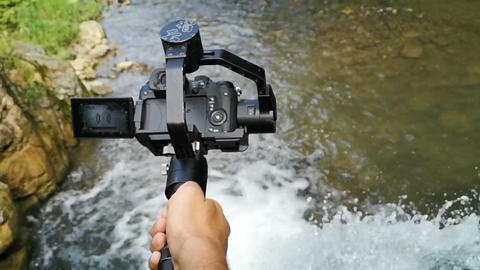 DSRL camera with electronical gimbal shooting waterfall in slow motion Footage