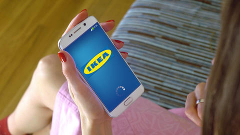 Young woman holding a cell phone with loading Ikea mobile app. Conceptual Footage