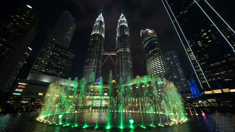 Petronas Twin Towers in Kuala Lumpur Downtown with fountain shows, Malaysia. Financial district and Live Action
