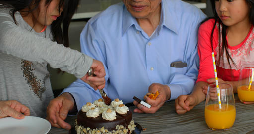 Front view of cute asian granddaughter cutting her birthday cake with knife in a comfortable home 4k Live Action
