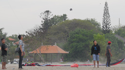 Men Lauching Kite With Long Tail,Sanur,Indonesia stock footage