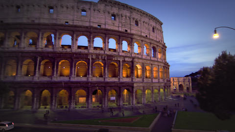 Tilt up from street to illuminated Colosseum at night Footage