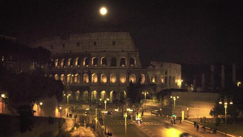 Full moon above illuminated Colosseum at night Footage